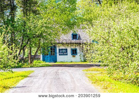 Ile D'Orleans Canada - June 1 2017: Blue house with roadin summer landscape French countryside with Vignoble vineyard or winery sign and dirt road