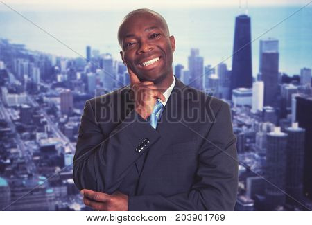 Laughing african american businessman with skyline of city in background
