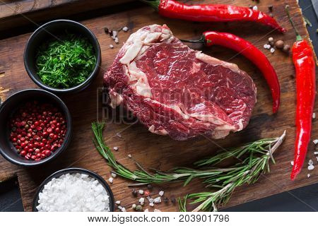 Raw rib eye steak with herbs, closeup. Cooking ingredients for restaurant dish. Fresh meat, spices and chilli on a wooden desk, top view