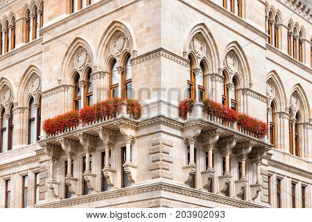 Symmetric detail of corner of cityhall historicism building in Vienna Austria. Neo-gothic windows and arches.