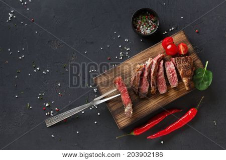 Rare rib eye steaks with herbs and spices on wooden board with meat fork, tomato and chilli at dark background with copy space, top view