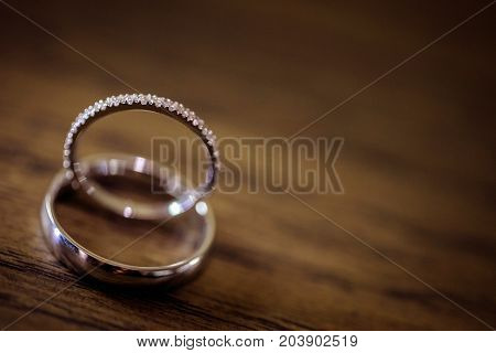 Wedding rings placed together on a rustic wooden surface as a symbol of marriage love and unity.