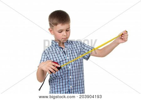 A small handsome builder boy in blue checkered shirt looks at a measuring tape, isolated on white background. Constructing concept