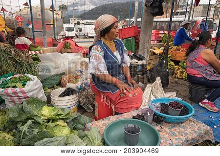 May 6 2017 Otavalo Ecuador: produce vendor in the Saturday market selling from street level