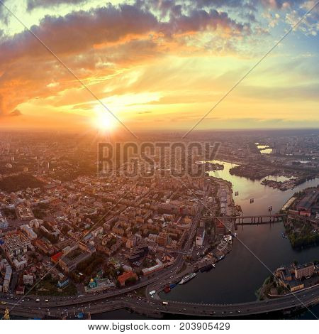 A big panorama of the city of Kiev on Podol at sunset. A modern metropolis in the center of Europe against the backdrop of a dramatic orange sky from a bird's eye view