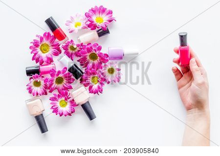 Choose nail polish for manicure. Woman hand hold bottle of polish on white background top view.