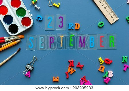September 23rd. Day 23 of month, Back to school concept. Calendar on teacher or student workplace background with school supplies on blue table. Autumn time.