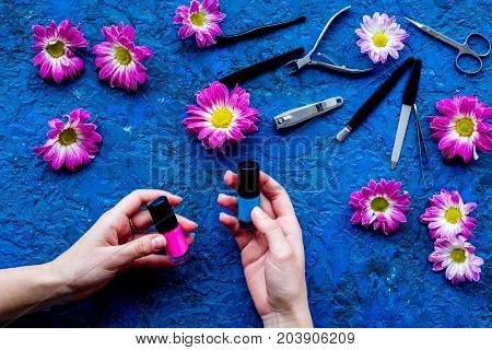 Choose nail polish for manicure. Woman hand hold bottle of polish on blue background top view.
