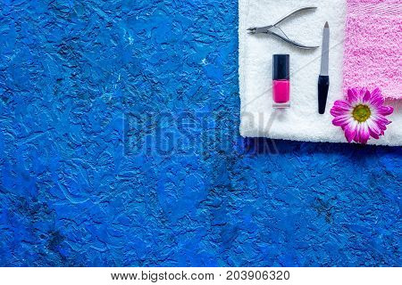 Manicure in beauty salon. Tools for manicure, nail polish and towels on blue desk top view.
