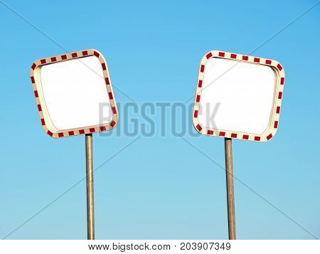 Two blank road mirrors on a blue sky background.