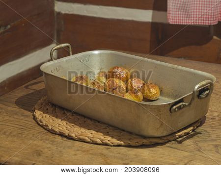 whole baked potatoes in rustic baking pan on wooden table in timbered farmhouse