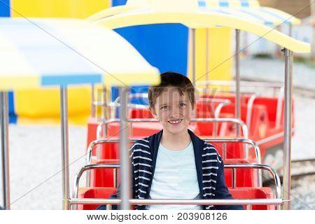 Happy Child Boy Having Fun In Amusement Park.