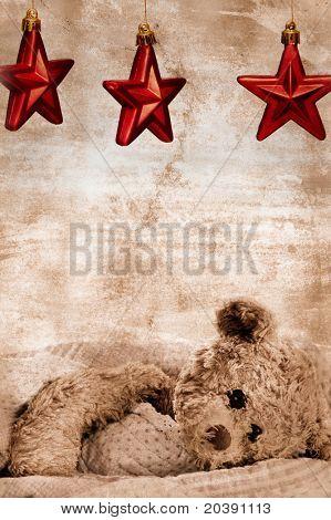 oso de peluche en Manta bajo tres estrellas de Navidad rojo sobre fondo grunge con copy space - genérico