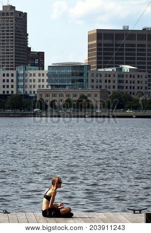 Boston, Massachusetts - August 16, 2017: Young girl sitting on the deck next to Charles River in Boston, Massachusetts.
