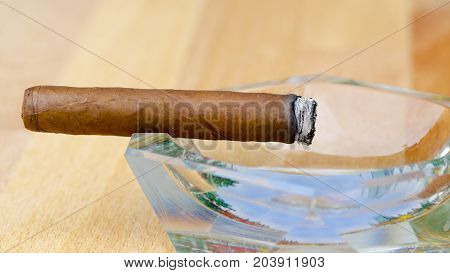 Close-up photo of a burning cigar in a glass ashtray with a blurred background