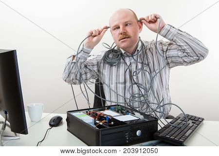 Irritated businessman touching cables on head while repairing computer in office