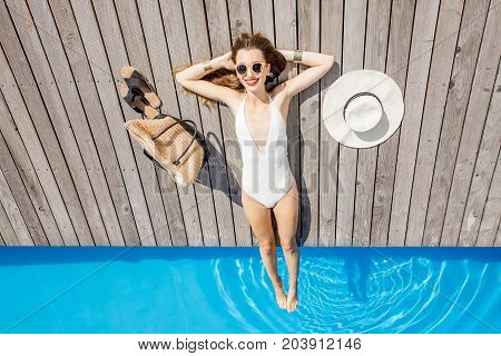Beautiful woman relaxing near the basin lying with hat and bag on the wooden poolside. Summer vacation and suntan concept