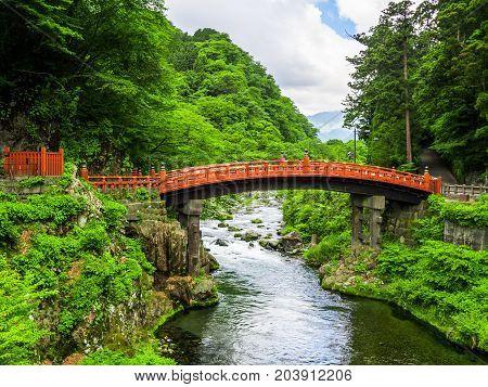 NIKKO, JAPAN - AUGUST 14, 2017 : Red Ancient Bridge, the Shinkyo bridge over the Daiwa river on a cloudy day, World heritage site, Nikko Tochigi Japan.