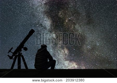 Man looking at the stars astronomy telescope. Milky Way starry sky