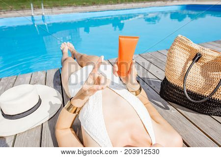 Woman in swimsuit applying sunscreen lotion lying near the basin outdoors. Sunscreen solar cream uv protection concept