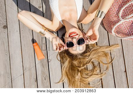 Portrait of a young beautiful woman relaxing with summer stuff on the wooden poolside outdoors near the basin. Summer vacation and suntan concept