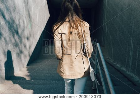Woman In A Beige Jacket And Jeans Descends Into The Underpass