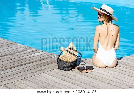 Beautiful young woman in hat relaxing near the swimming pool sitting back with bag and slippers on the wooden poolside
