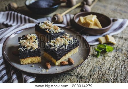 Sponge Cake With Poppy Seed Layer, Decorated With White Chocolate Curls And Sliced Almond