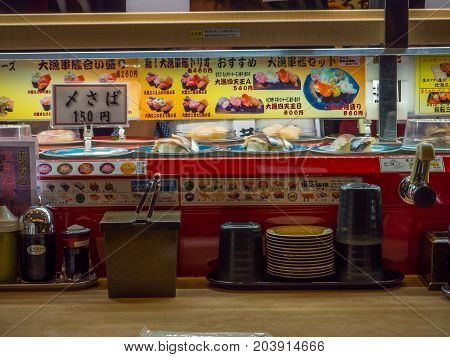 TOKYO, JAPAN -28 JUN 2017: View of assorted japanesse food over a table, inside of a kaitenzushi conveyor belt sushi restaurant in Tokyo, Japan.