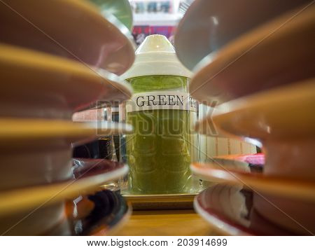 TOKYO, JAPAN -28 JUN 2017: Close up of a green tea inside of a flask, with a blurred plates pilled in front, inside of a kaitenzushi conveyor belt sushi restaurant in Tokyo.