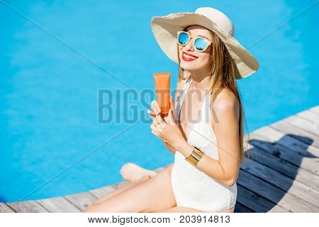Portrait of a young woman in sunhat and swimsuit holding a tube with sunscreen lotion at the swimming pool