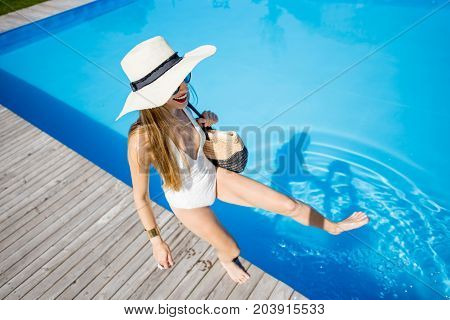 Lifestyle portrait of a woman in swimsuit with sunhat and bag playing with water on the swimming pool