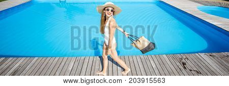Lifestyle portrait of a woman in swimsuit with sunhat and bag walking outdoors near the swimming pool. Cropped panoramic image
