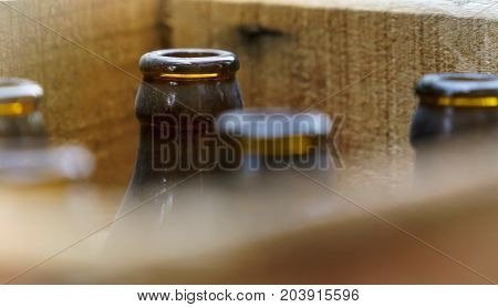 Old beer bottles in a wooden crate on display outside a shop.