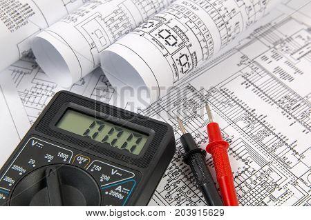 paper electrical engineering drawings and digital multimeter