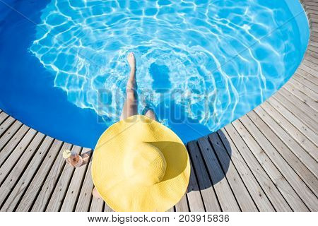 Woman in big yellow sunhat with cocktail drink relaxing at the round swimming pool with blue water outdoors. Top view