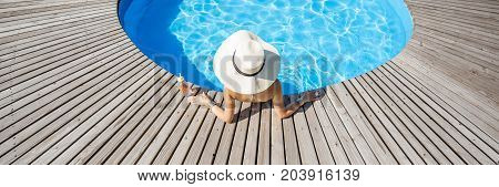 Woman in big sunhat with cocktail drink relaxing at the round swimming pool with blue water outdoors. Top view