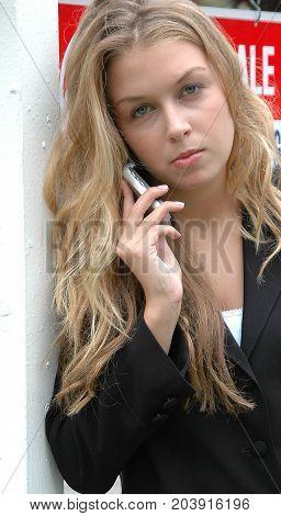 Female beauty fashion model talking on her cellphone outside.
