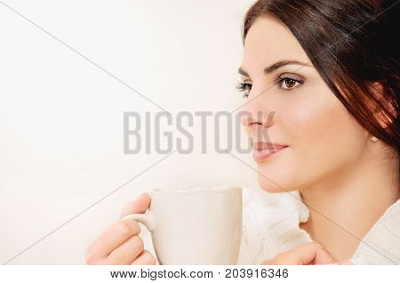 Young Woman With Long Hair And Brown Eyes Drinking Coffee Or Tea From A Cup