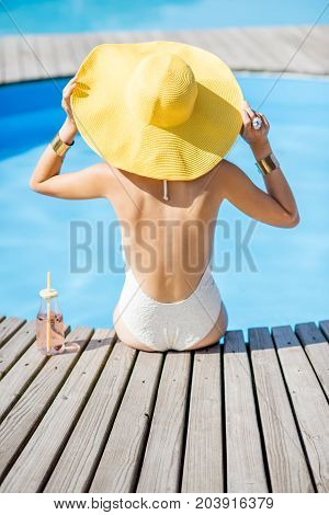 Young woman in swimsuit with big yellow sunhat relaxing with a bottle of fresh drink sitting back on the poolside outdoors