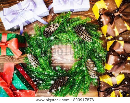 Christmas wreath of fir branches with cones along with gift boxes on the wooden background. Drawn snow. Top view. Holiday concept