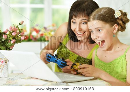 Smiling mother and daughter sitting at table and playing computer game on laptop
