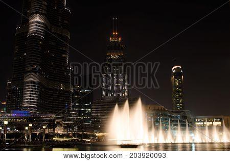 DUBAI UNITED ARAB EMIRATES - 10 SEPTEMBER 2017: Dubai Fountains world's largest choreographed fountain system live show near Burj Khalifa and abra on lake in night