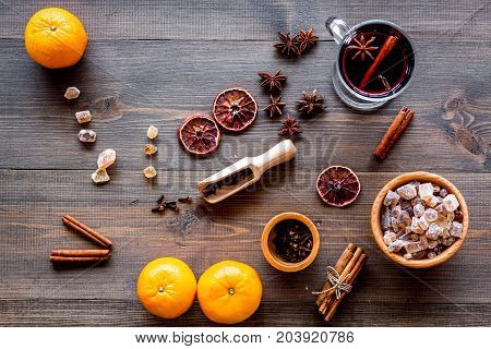 Hot mulled wine or grog cooking for new year celebration with oranges and spices ingredients on wooden table background flat lay
