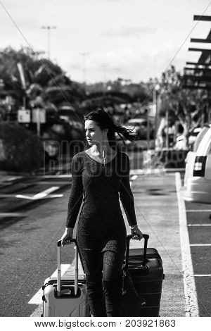 woman in sexy dress and boots walking and rolling two travel bags wheeled suitcases on asphalt road on sunny summer day on cityscape background black and white