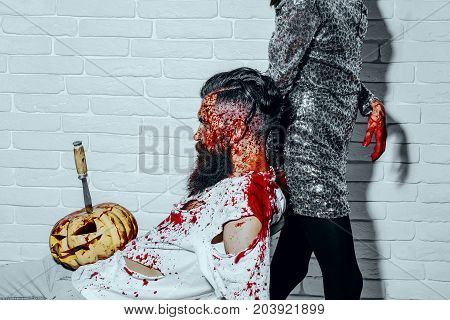 Halloween man sitting with pumpkin stabbed with knife. Bearded hipster with red blood splatters on white brick wall. Female maniac in silver dress with bloody hands. Halloween holiday concept