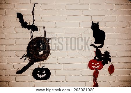 Halloween holiday celebration symbols. Black and red pumpkins cat bat tree leaves and nest silhouette paper cutouts on beige brick wall. Mystery and superstition concept.