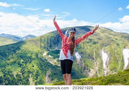 Summer hiking in the mountains. Young tourist girl with long hair in a cap with hands up on the top of the mountains admires the nature. Travel concept