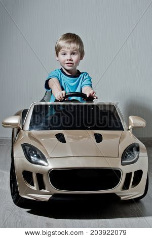 Traveling and education. Car with small boy. Happy kid in toy car. Childhood and happiness. Child driver in auto.