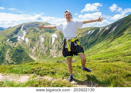 Summer hiking in the mountains. Young tourist man in a cap with hands up on the top of the mountains admires the nature. Travel concept